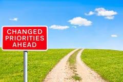 Priorités de panneau routier changées en avant Image stock