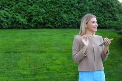Les prises blondes mignonnes téléphonent dans des mains, regards autour et sourient énigme image stock