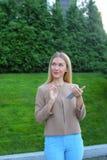 Les prises blondes mignonnes téléphonent dans des mains, regards autour et sourient énigme photos libres de droits