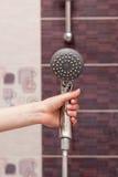 Les prises de femme au foyer dans sa main cleen et  de Ñ losed outre du pommeau de douche de pluie dans la salle de bains photos stock