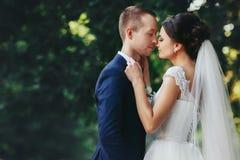 Les prises de jeune mariée toilettent le noeud papillon du ` s se penchant à son visage photos libres de droits