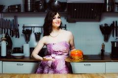 Les prises de sourire d'hôtesse durcissent comme le grand beignet avec le fondant Photographie stock