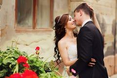 Les prises de sourire de jeune mariée toilettent le chef du ` s tandis qu'il l'embrasse derrière un Re image libre de droits