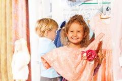 Les prises riantes de fille s'habillent, garçon derrière elle dans la boutique Photographie stock