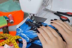 Les processus de la couture sur la machine à coudre cousent la machine à coudre de mains femelles machine à coudre et ciseaux fem Image stock