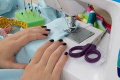 Les processus de la couture sur la machine à coudre cousent la machine à coudre de mains femelles machine à coudre et ciseaux fem Photographie stock