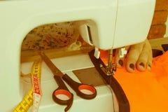 Les processus de la couture sur la machine à coudre cousent le sewi de mains du ` s de femmes Images stock