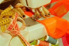 Les processus de la couture sur la machine à coudre cousent le sewi de mains du ` s de femmes Photo stock
