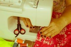 Les processus de la couture sur la machine à coudre cousent le sewi de mains du ` s de femmes Image stock