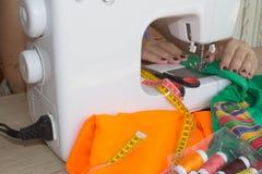 Les processus de la couture sur la machine à coudre cousent la machine à coudre de mains du ` s de femmes Tailleur féminin fileta Image libre de droits