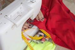 Les processus de la couture sur la machine à coudre cousent la machine à coudre de mains du ` s de femmes Tailleur féminin fileta Image stock