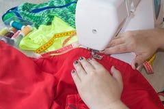 Les processus de la couture sur la machine à coudre cousent la machine à coudre de mains du ` s de femmes Tailleur féminin fileta Photographie stock libre de droits
