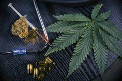 Les produits médicaux de marijuana avec des cannabis poussent des feuilles sur le noir Photographie stock libre de droits