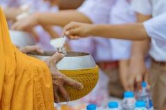 Les professeurs et les ?tudiants font ensemble le m?rite pour donner des offres de nourriture ? un moine bouddhiste des jours rel photographie stock