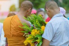 Les professeurs et les ?tudiants font ensemble le m?rite pour donner des offres de nourriture ? un moine bouddhiste des jours rel images libres de droits