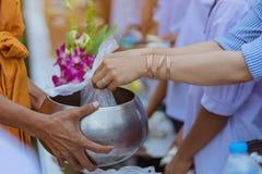Les professeurs et les ?tudiants font ensemble le m?rite pour donner des offres de nourriture ? un moine bouddhiste des jours rel photo stock