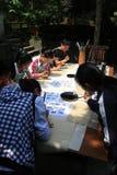 Les professeurs sont enseignant à des enfants comment écrire le callig photo libre de droits