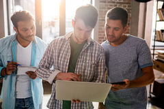 Les professionnels travaillant aux affaires nouvelles projettent avec l'ordinateur portable dans le bureau de petite entreprise Photo libre de droits