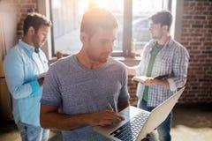 Les professionnels travaillant aux affaires nouvelles projettent avec l'ordinateur portable dans le bureau de petite entreprise Image libre de droits