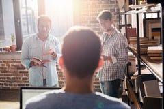 Les professionnels travaillant aux affaires nouvelles projettent avec l'ordinateur portable et les livres dans le bureau de petit Image libre de droits