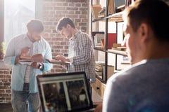 Les professionnels travaillant aux affaires nouvelles projettent avec l'ordinateur portable et les livres dans le bureau de petit Images libres de droits