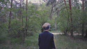 Les promenades de jeune femme dans le bel appareil-photo rêveur de forêt suit clips vidéos