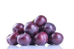 les prunes délicieuses mûres empilées dans une pile sur un blanc ont isolé le fond photos stock