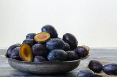 Les prunes de quetsche sont dans la tasse de cuivre antique photo stock