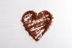 Les puces de chocolat ont arrangé dans une forme de coeur sur le fond en bois Photographie stock libre de droits