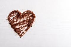 Les puces de chocolat ont arrangé dans une forme de coeur sur le fond en bois Photographie stock