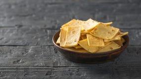 Les puces de tortilla mexicaines avec du fromage dans un argile roulent sur une table en bois rustique Copiez l'espace images stock
