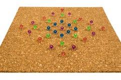 Les punaises colorées dans Corkboard ont isolé sur le blanc Photo stock