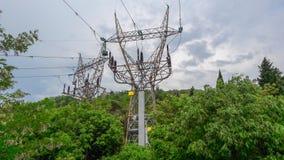 Les pylônes à haute tension d'elecricity viennent en dehors d'une forêt verte photographie stock