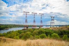 Les pylônes électriques traversent la rivière image libre de droits