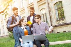 Les quatre amis mignons détendent près de l'université Image stock