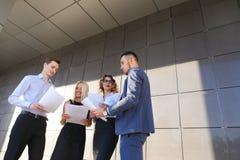 Les quatre jeunes, deux hommes et deux femmes, étudiantes, communiquent, Image stock