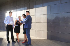 Les quatre jeunes, deux hommes et deux femmes, étudiantes, communiquent, Photographie stock