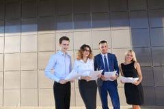 Les quatre jeunes, deux hommes et deux femmes, étudiantes, communiquent, Images libres de droits