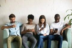 Les quatre jeunes s'asseyant sur le divan absorbé par des smartphones images libres de droits