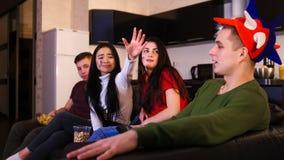 Les quatre jeunes s'asseyant sur le sofa et le match de football de observation Un homme jugeant la TV à distance et une femme ve images stock