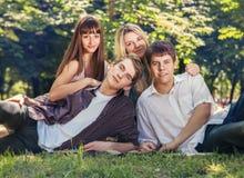 Les quatre jeunes sur la pelouse verte en parc Images libres de droits