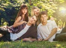 Les quatre jeunes sur la pelouse verte en parc Image libre de droits