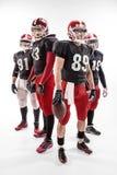 Les quatre joueurs de football américain posant avec la boule sur le fond blanc images libres de droits