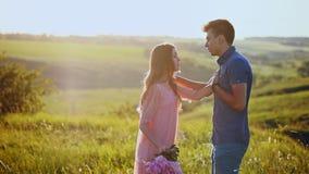 Les querelles de fille avec le type, jette des fleurs à l'homme et aux feuilles banque de vidéos