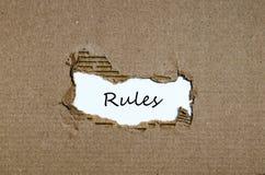 Les règles de mot apparaissant derrière le papier déchiré Photographie stock