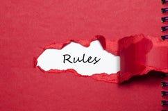 Les règles de mot apparaissant derrière le papier déchiré Photos stock