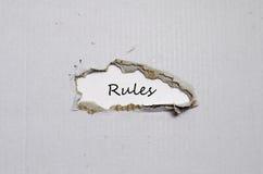 Les règles de mot apparaissant derrière le papier déchiré Images stock