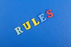 Les RÈGLES expriment sur le fond bleu composé des lettres en bois d'ABC de bloc coloré d'alphabet, copient l'espace pour le texte photos stock