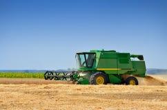 Les récoltes de machines agricoles de la céréale cultive dans le domaine Photos libres de droits