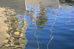 Les réflexions abstraites des bateaux et des bâtiments dans le bleu ont ondulé l'eau Photos libres de droits